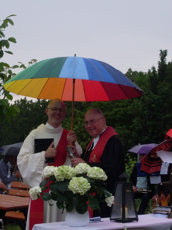 Ökumenische Andacht am Weißen Kreuz, Diakon Rebitzer und Pfarrer Eyßelein unterm Regenschirm