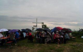 Ökumenische Andacht am Weißen Kreuz unterm Regenschirm